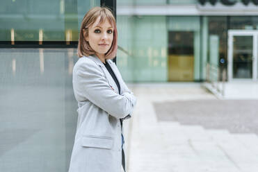 Portrait of confident busineswoman leaning against glass building - KIJF02815