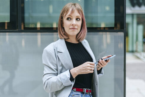 Portrait of woman with cell phone at glass building - KIJF02818