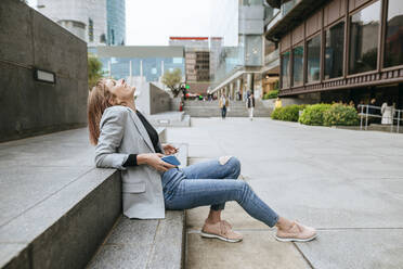 Happy woman sitting on stairs  in the city with cell phone leaning back - KIJF02824