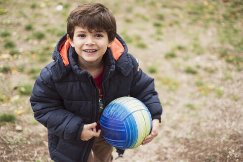 Portrait of smiling little boy with ball standing on a meadow - JASF02080