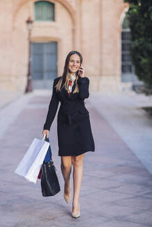 Portrait of happy young woman on the phone walking in the city with shopping bags - DLTSF00281