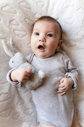 Baby girl lying on a white blanket with clouds and holding a rabbit toy - GEMF03300