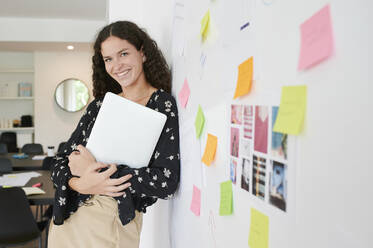 Portait of smiling young businesswoman leaning against a wall full of sticky notes in an office - IGGF01466