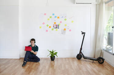 Young businessman wearing headphones and using a digital tablet while sitting on the floor in a modern office - IGGF01469