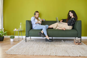 Two smiling young businesswomen sitting on couch in modern office - IGGF01475