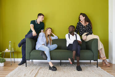 Casual colleagues talking on a sofa in a green walled office lounge - IGGF01478