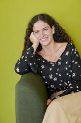Portrait of smiling young woman sitting on green couch - IGGF01481