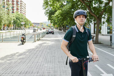 Casual young businessman riding e-scooter on bicycle lane in the city - IGGF01490