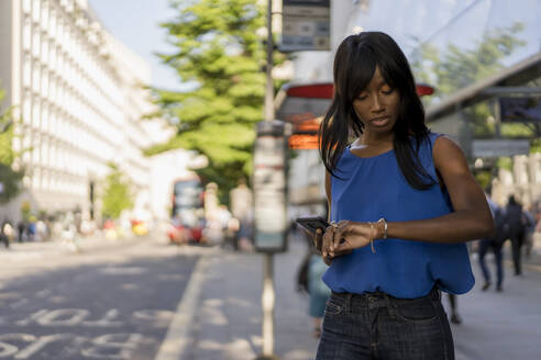 Female Afro-American using smartphone and checking the time at bus stop in London, United Kingdom - MAUF03063