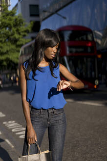 Female Afro-American checking the time in the city - MAUF03069
