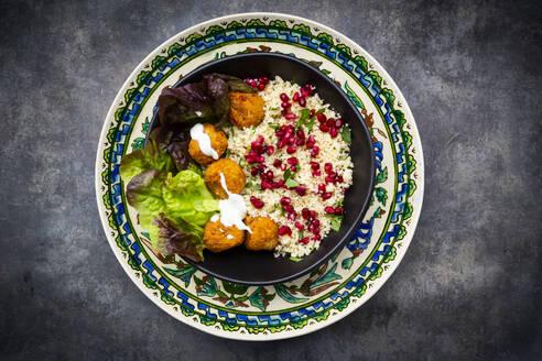 Bowl offalafelwith lettuce, yogurt, pomegranate seeds, parsley, mint and Tabbouleh salad - LVF08434
