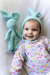 Baby girl with bunny hat and a bunny toy lying on bed - GEMF03306