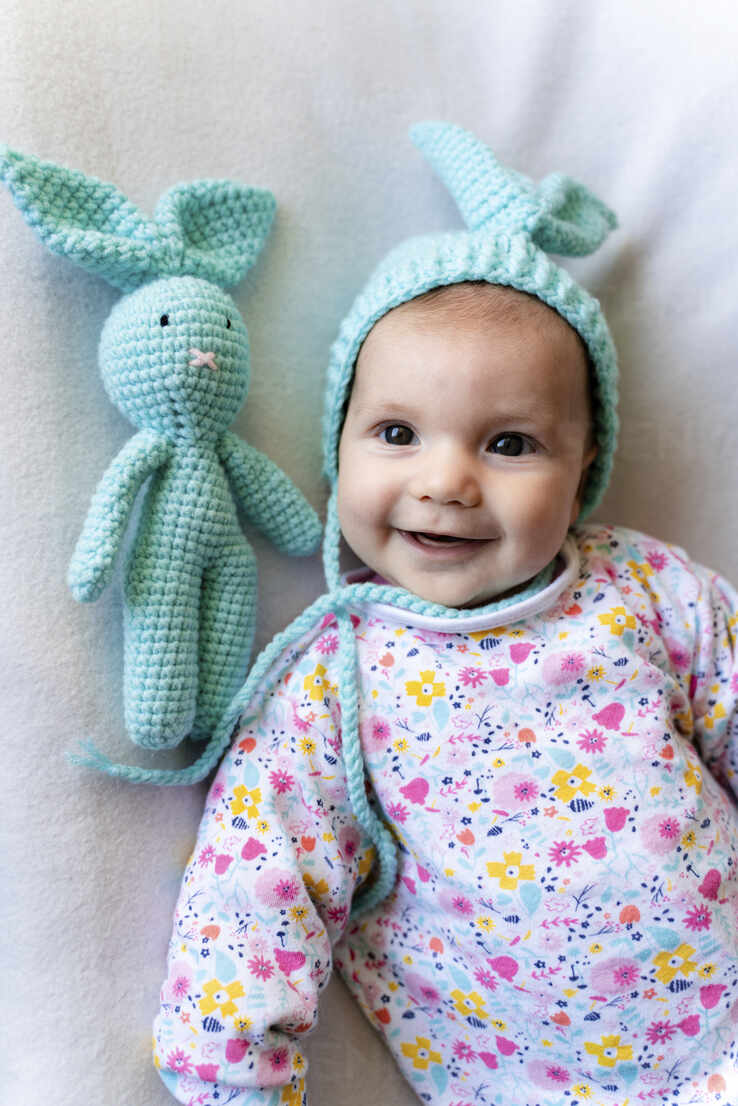 Baby girl with bunny hat and a bunny toy lying on bed - GEMF03306 - Gemma Ferrando/Westend61