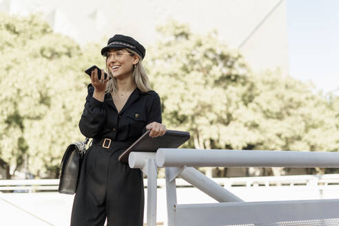 Young blond businesswoman wearing black hat and holding laptop bag and using smartphone - ERRF02079