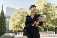Young blond businesswoman wearing black sailor's cap and holding laptop bag - ERRF02082