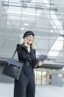 Young blond businesswoman wearing black sailor's cap, holding laptop bag and using smartphone - ERRF02085
