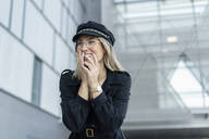 Young blond businesswoman wearing black sailor's cap and laughing - ERRF02091