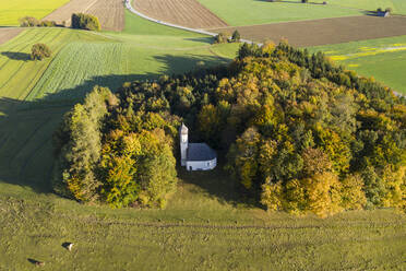 Germany, Bavaria, Ascholding, Aerial view of Saint Georg Chapel hidden in autumn grove - LHF00757