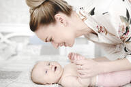 Mother with her cute smiling baby girl in the bedroom - EYAF00671