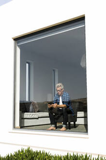 Casual businessman sitting in modern home looking at tablet - SBOF02030