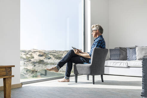 Casual businessman sitting in modern home using tablet - SBOF02036