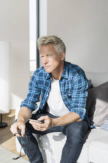 Casual businessman sitting in modern home holding smartphone - SBOF02042