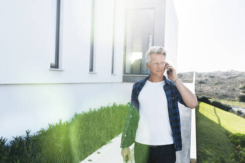 Casual man outside his modern home talking on the phone - SBOF02048