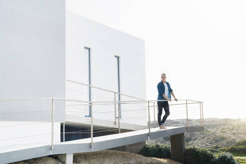 Casual man standing in front of his modern home looking at the landscape - SBOF02051