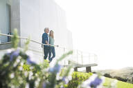 Smiling couple standing in front of their modern looking at the landscape - SBOF02054