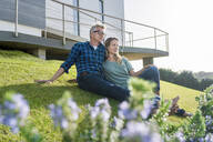 Smiling couple stitting in front of their modern home looking at the landscape - SBOF02057