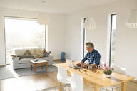 Casual businessman working on his laptop in home office looking at woman lying on sofa - SBOF02060