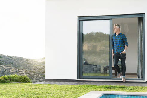 Casual man standing in front of his modern home with pool looking at the landscape - SBOF02063