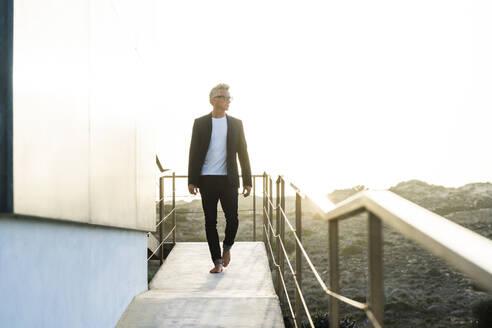 Businessman walking along his modern home looking around - SBOF02069
