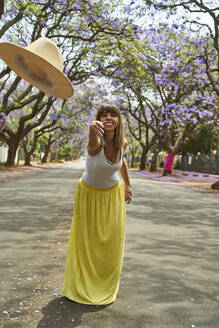 Woman throwing a hat in the middle of a street full of jacaranda trees in bloom, Pretoria, South Africa - VEGF00796