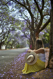 Woman leaning on a tree at a street with jacaranda trees in bloom, Pretoria, South Africa - VEGF00799