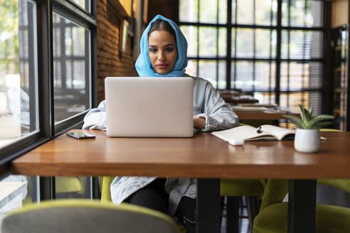 Businesswoman wearing turquoise hijab in a cafe and working, using laptop - ERRF02103