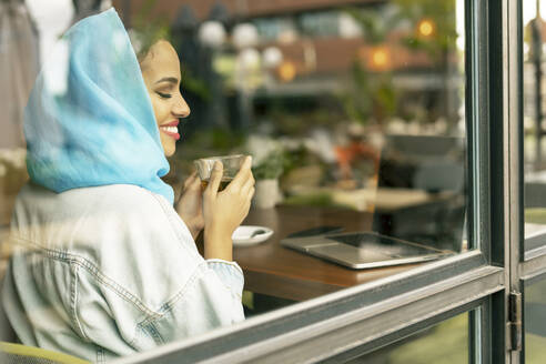 Young woman wearing turquoise hijab and drinking tea in a cafe, looking through window - ERRF02121
