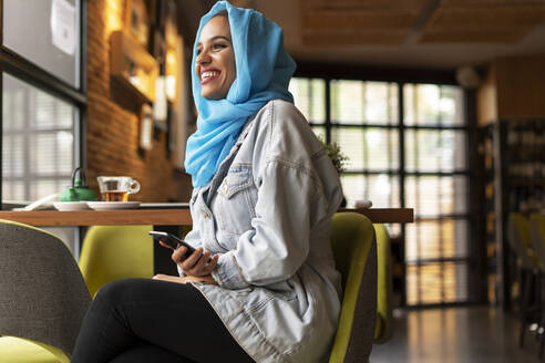 Young woman wearing turquoise hijab and using smartphone in a cafe - ERRF02136