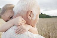 Granddaughter hugging her grandfather outdoors - EYAF00690