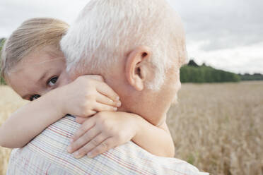Granddaughter hugging her grandfather outdoors - EYAF00690