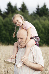 Portrait of happy little girl on grandfather's shoulders in an oat field - EYAF00696