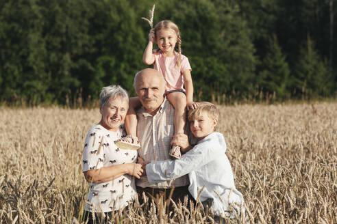 Family portrait of grandparents with their grandchildren in an oat field - EYAF00699