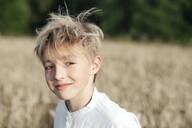 Portrait of smiling blond boy in an oat field - EYAF00702