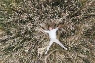 Blond boy lying outstretched in an oat field - EYAF00705