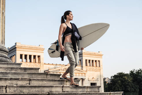 Young woman with surfboard on the way to Eisbach, Munich, Germany - WFF00178