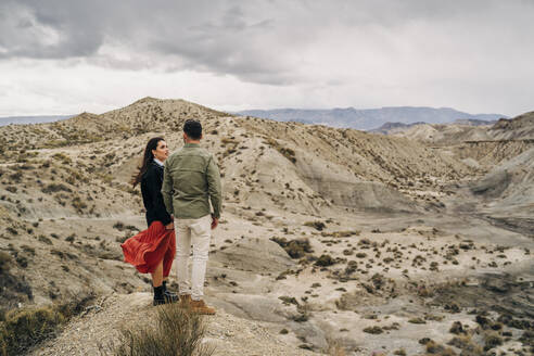 Young couple in desert landscape under cloudy sky, Almeria, Andalusia, Spain - MPPF00245