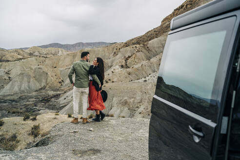 Young couple in desert landscape under cloudy sky next to camper van, Almeria, Andalusia, Spain - MPPF00248