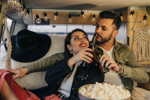 Happy young couple clinking beer bottles inside camper van - MPPF00254