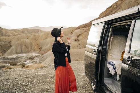 Young woman in desert landscape standing next to camper van, Almeria, Andalusia, Spain - MPPF00257