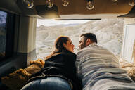 Young couple on a trip lying in a camper van at sunset, Almeria, Andalusia, Spain - MPPF00266